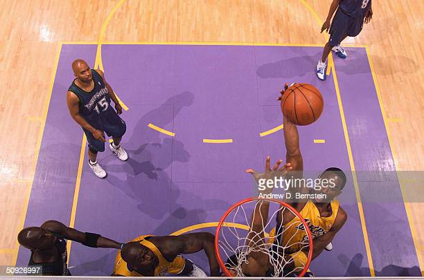 Kobe Bryant of the Los Angeles Lakers shoots as teammate Shaquille O'Neal watches along with Kevin Garnett and Darrick Martin of the Minnesota...