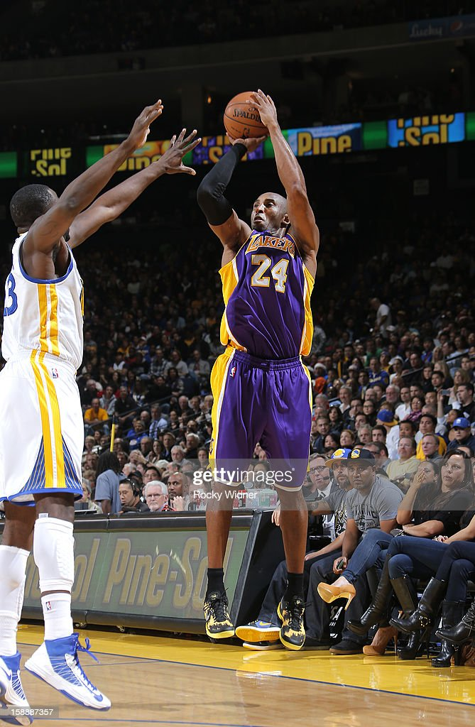 Kobe Bryant #24 of the Los Angeles Lakers shoots over Draymond Green #23 of the Golden State Warriors on December 22, 2012 at Oracle Arena in Oakland, California.