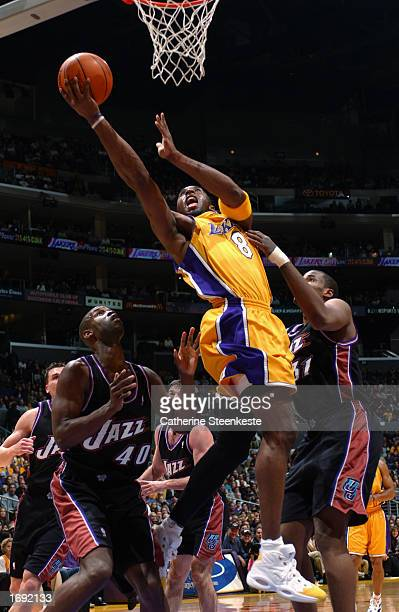 Kobe Bryant of the Los Angeles Lakers shoots while under pressure from Calbert Cheaney and Jarron Collins of the Utah Jazz during a game at Staples...