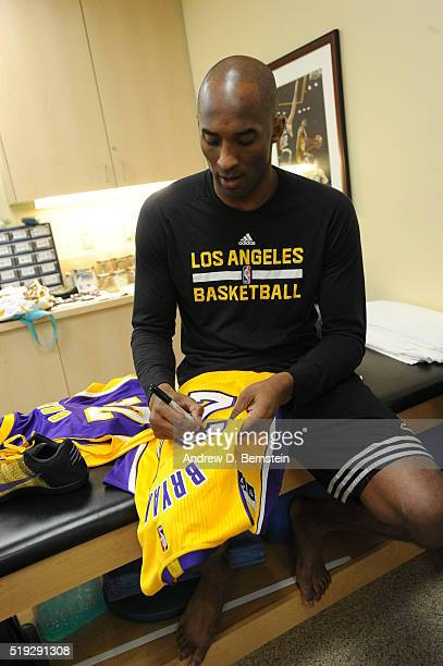 Kobe Bryant of the Los Angeles Lakers signs a jersey before the game against the Los Angeles Clippers on April 5 2016 at STAPLES Center in Los...