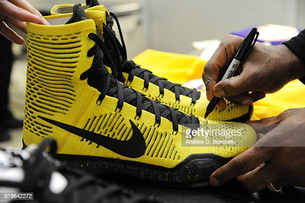 Kobe Bryant of the Los Angeles Lakers signs a pair of sneakers after the game against the Los Angeles Clippers on April 5 2016 at STAPLES Center in...