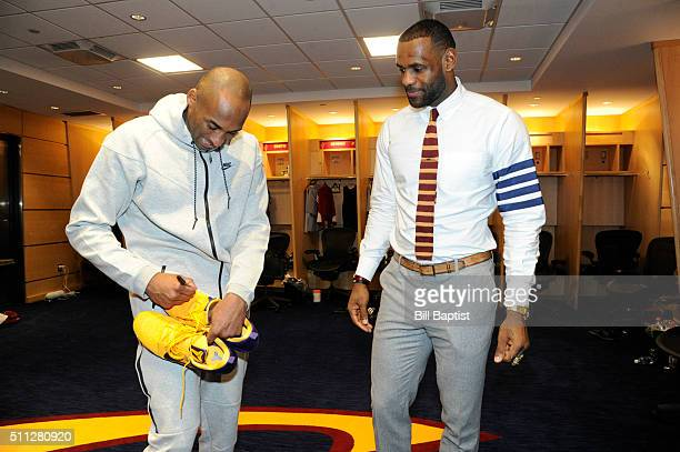 Kobe Bryant of the Los Angeles Lakers signs a pair of sneakers for LeBron James of the Cleveland Cavaliers in the locker room after the game at The...