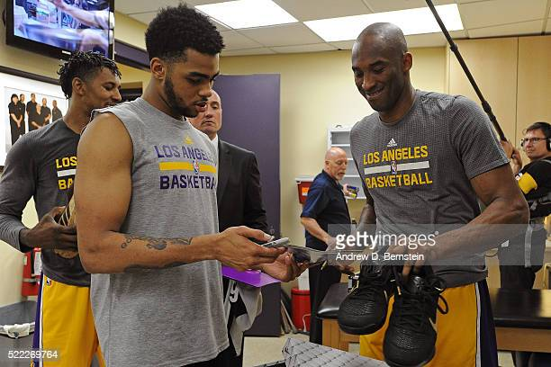 Kobe Bryant of the Los Angeles Lakers signs a shoes for D'Angelo Russell before the game against the Utah Jazz at STAPLES Center on April 13 2016 in...
