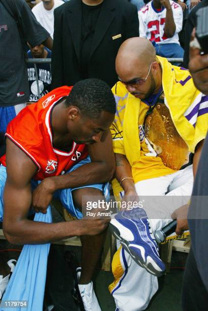 Kobe Bryant of the Los Angeles Lakers signs an autograph for announcer Booby Smooth 'the Politician' during Summer Playground ball on July 18 2002 at...