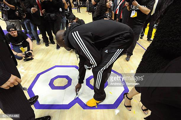 Kobe Bryant of the Los Angeles Lakers signs the court after his last game against the Utah Jazz at STAPLES Center on April 13, 2016 in Los Angeles,...