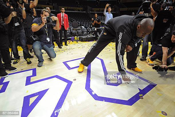 Kobe Bryant of the Los Angeles Lakers signs the court after his last game against the Utah Jazz at STAPLES Center on April 13 2016 in Los Angeles...