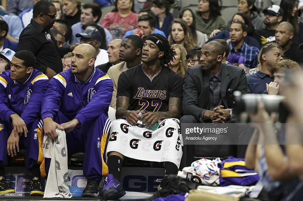 Kobe Bryant (R) of the Los Angeles Lakers sits on the sideline during a game against the Dallas Mavericks on December 26, 2014 at the American Airlines Center in Dallas, Texas.