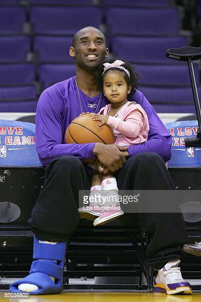 Kobe Bryant of the Los Angeles Lakers sits with his daughter Natalia before the game against the Minnesota Timberwolves as he recovers from an ankle...