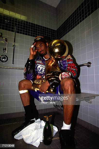 Kobe Bryant of the Los Angeles Lakers sits with the NBA Championship trophy after defeating the Philadelphia 76ers to win the 2001 NBA title on June...