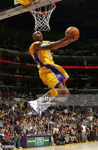 Kobe Bryant of the Los Angeles Lakers slam dunks against the New Orleans Hornets on December 22 2004 at the Staples Center in Los Angeles California...