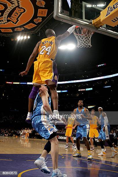 Kobe Bryant of the Los Angeles Lakers slam dunks over Eduardo Najera of the Denver Nuggets in the second half of Game Two of the Western Conference...