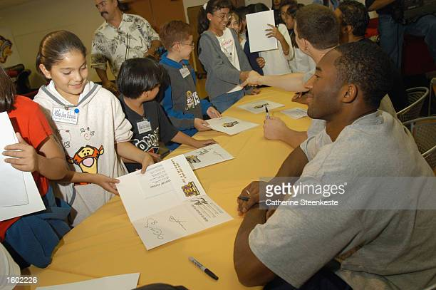 Kobe Bryant of the Los Angeles Lakers smiles after giving an autograph to a young female fan at the NBA's official Read to Achieve Week at Miles...