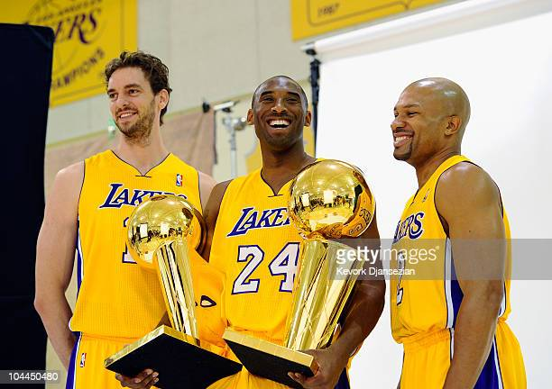 Kobe Bryant of the Los Angeles Lakers smiles as he holds two NBA Finals Larry O'Brien Championship Trophy's as he poses for a photograph with...