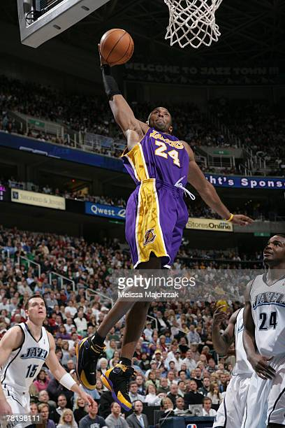 Kobe Bryant of the Los Angeles Lakers soars for a dunk over Paul Millsap of the Utah Jazz at EnergySolutions Arena November 30 2007 in Salt Lake City...