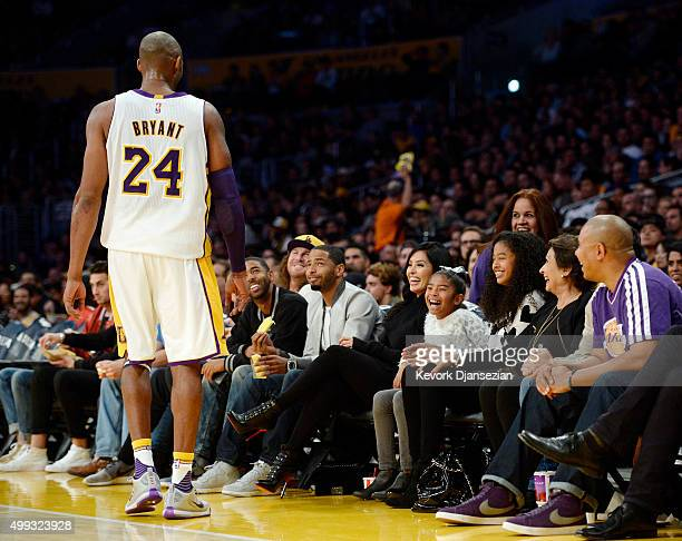 Kobe Bryant of the Los Angeles Lakers speaks with his daughters Gianna Natalia and wife Vanessa during the basketball game against the Indiana Pacers...