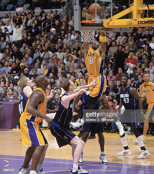 Kobe Bryant of the Los Angeles Lakers takes the ball up for the dunk over Shawn Bradley of the Dallas Mavereicks during the game at Staples Center on...