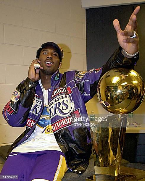 Kobe Bryant of the Los Angeles Lakers talks on his cell phone next to the NBA championship trophy after winning game five of the NBA Finals against...