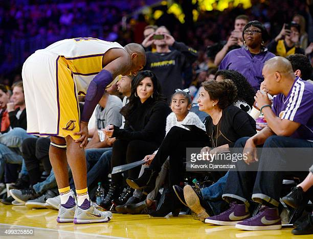 Kobe Bryant of the Los Angeles Lakers talks with a family member as wife Vanessa Laine Bryant and daughters Gianna Bryant and Natalia Bryant look on...