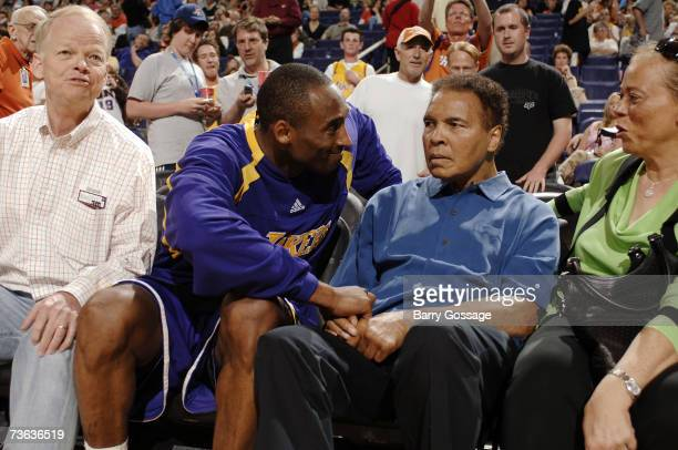 Kobe Bryant of the Los Angeles Lakers talks with former boxing great Muhammad Ali and his wife Lonnie Ali as the Phoenix Suns host the Los Angeles...