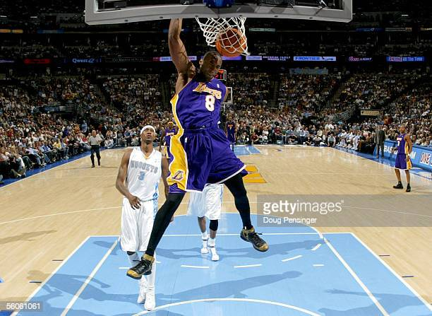 Kobe Bryant of the Los Angeles Lakers throws down a dunk after breaking away from DerMarr Johnson of the Denver Nuggets on November 2 2005 at the...