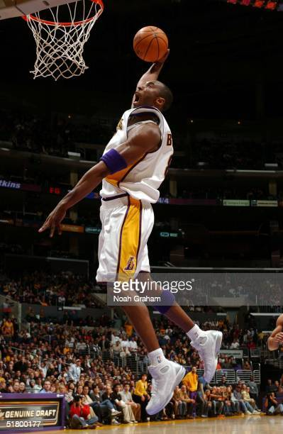 Kobe Bryant of the Los Angeles Lakers throws down a dunk against the New Orleans Hornets at the Staples Center on November 28 2004 in Los Angeles...