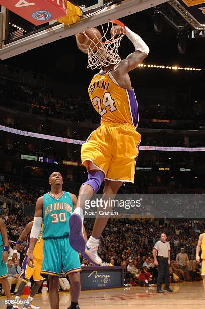 Kobe Bryant of the Los Angeles Lakers throws down a reversedunk while David West of the New Orleans Hornets looks on during their game at Staples...
