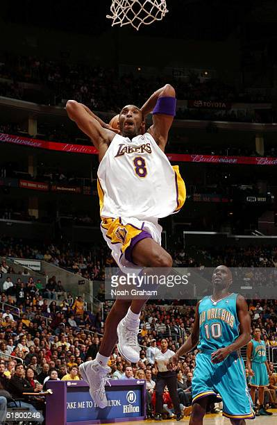 Kobe Bryant of the Los Angeles Lakers throws dunk against the New Orleans Hornets at the Staples Center on November 28, 2004 in Los Angeles,...
