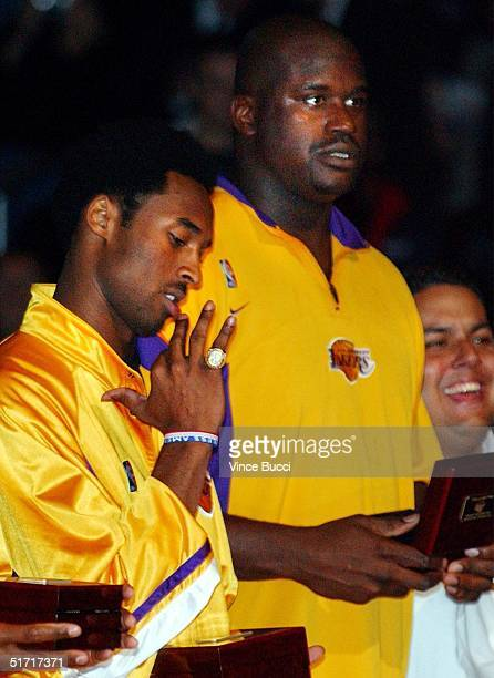 Kobe Bryant of the Los Angeles Lakers tries on his ring as teammate Shaquille O'Neal looks on during a ceremony October 30 2001 in Los Angeles CA The...