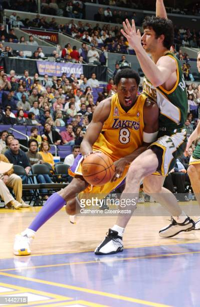Kobe Bryant of the Los Angeles Lakers tries to get to the basket past Vladimir Radmanovic of the Seattle SuperSonics during the second half of action...