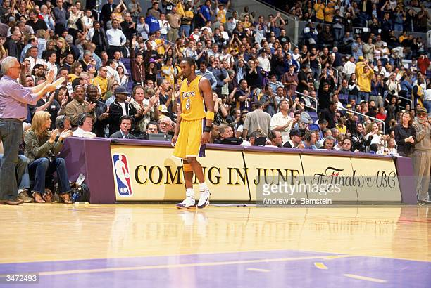 Kobe Bryant of the Los Angeles Lakers walks back to the team bench during Game 2 of the opening round of the 2004 NBA Playoffs against the Houston...