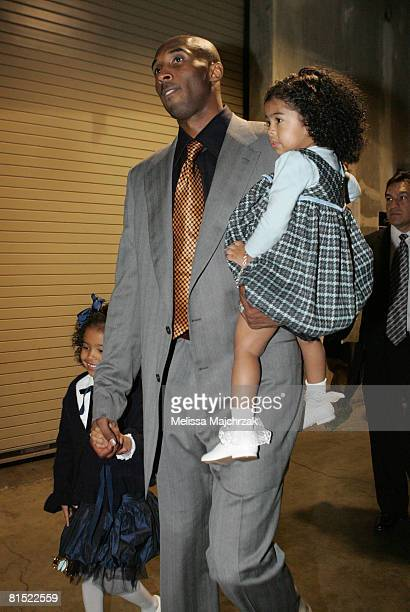 Kobe Bryant of the Los Angeles Lakers walks out of the arena with his daughters Natalia and Gianna following his team's victory over the Boston...