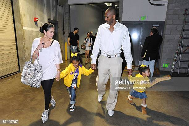 Kobe Bryant of the Los Angeles Lakers walks out of the arena with his wife Vanessa and his daughters Natalia and Gianna following his team's victory...