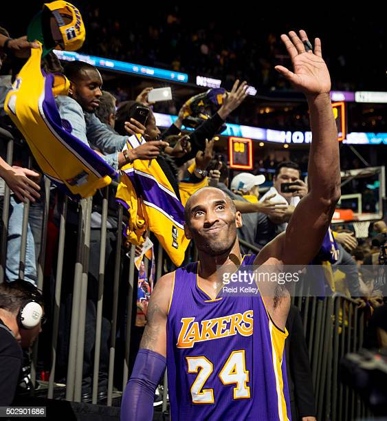 Kobe Bryant of the Los Angeles Lakers waves as he walks off the court after the gamea against the Charlotte Hornets on December 28 2015 at Time...