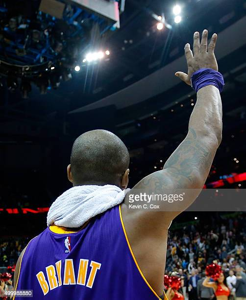 Kobe Bryant of the Los Angeles Lakers waves to the fans after their 10087 loss to the Atlanta Hawks at Philips Arena on December 4 2015 in Atlanta...