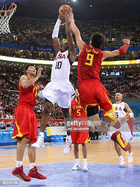 Kobe Bryant of the United States goes up for a dunk between Yi Jianlian and Sun Yue of China during the day 2 preliminary game at the Beijing 2008...