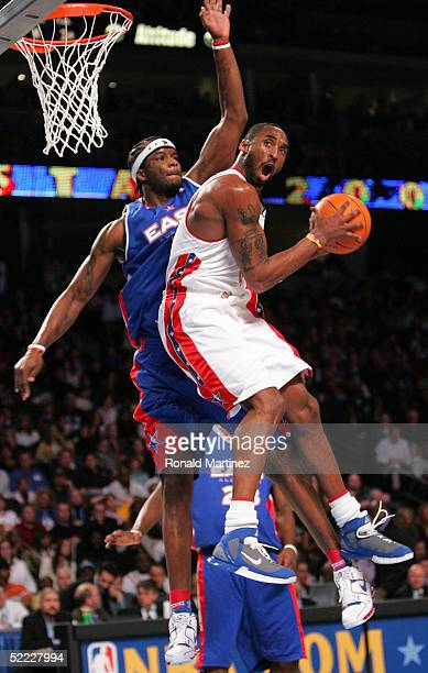 Kobe Bryant of the Western Conference AllStars goes to the basket against Jermaine O'Neal of the Eastern Conference AllStars during the 54th AllStar...