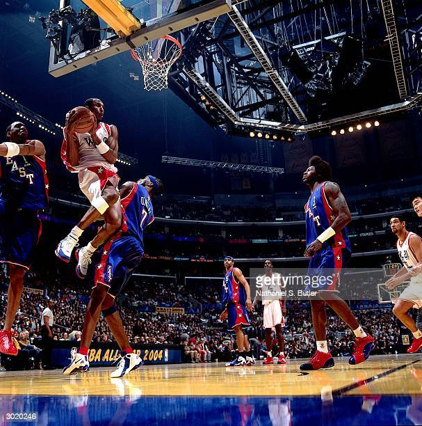 Kobe Bryant of the Western Conference AllStars splits the defense of Jermaine O'Neal and Tracy McGrady of the Eastern Conference AllStars during the...