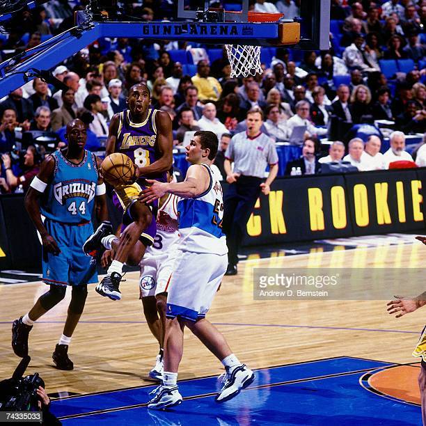 Kobe Bryant of the Western Conference attempts a layup against Vitally Potapenko of the Eastern Conference during the 1997 Rookie Game played...