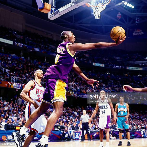 Kobe Bryant of the Western Conference attempts a reverse layup against Kerry Kittles of the Eastern Conference during the 1997 Rookie Game played...