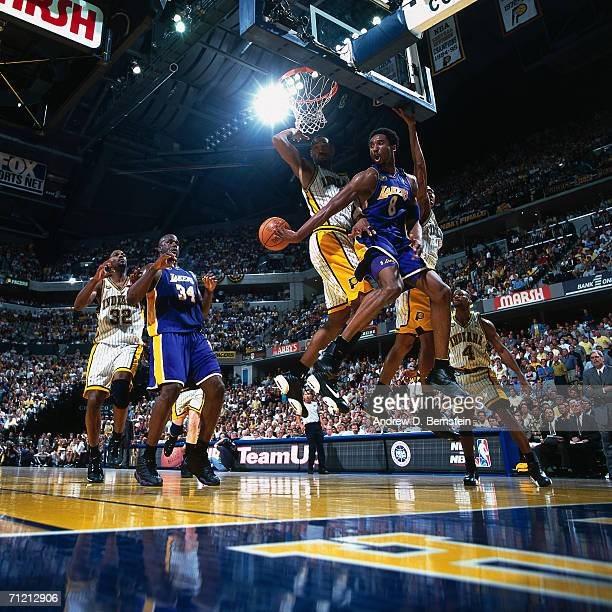 Kobe Bryant passes to teammate Shaquille O'Neal of the Los Angeles Lakers against Travis Best of the Indiana Pacers during a game in 2000 at Conseco...