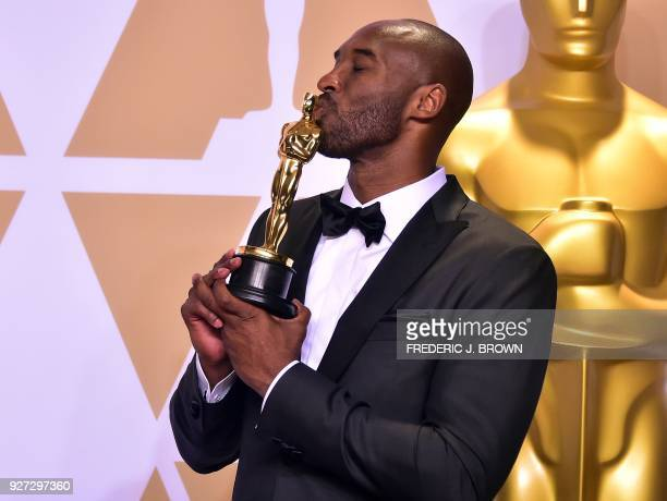 TOPSHOT Kobe Bryant poses in the press room with the Oscar for Best Animated Short Film for 'Dear Basketball' during the 90th Annual Academy Awards...