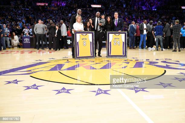 Kobe Bryant poses with his family and Earvin Johnson Rob Pelinka and Jeanie Buss at halftime after both his and Los Angeles Lakers jerseys are...