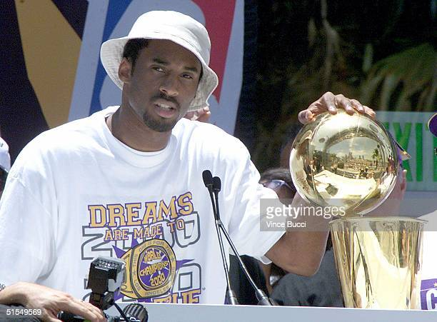 Kobe Bryant puts his hand on the NBA championship trophy at the end of the Los Angeles Lakers victory parade through downtown Los Angeles 21 June...