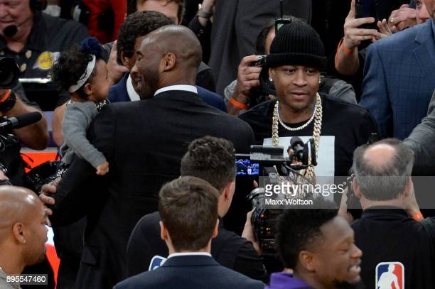 Kobe Bryant stands alongside Allen Iverson at halftime after both of Bryant's and Los Angeles Lakers jerseys are retired at Staples Center on...
