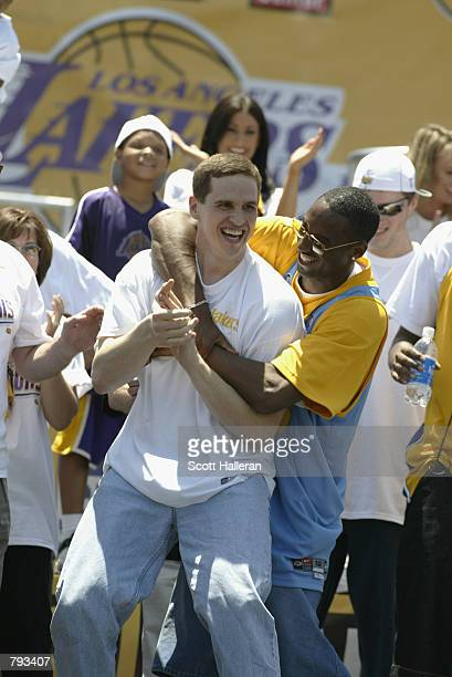Kobe Byant hugs Mark Madsen of the Los Angeles Lakers after dancing for the crowd gathered at the Staples Center following the victory parade on June...