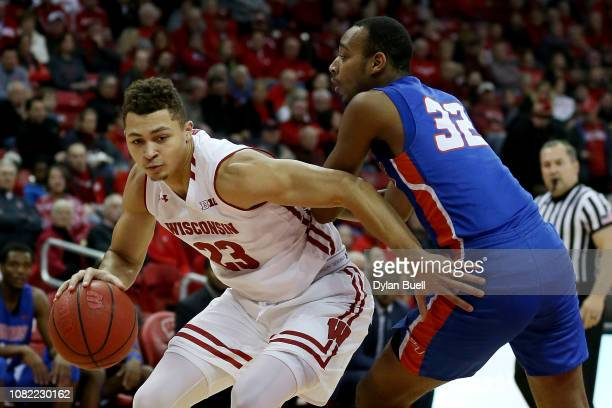 Kobe King of the Wisconsin Badgers dribbles the ball while being guarded by Chris Dubose of the Savannah State Tigers in the first half at the Kohl...