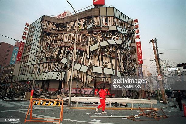 A Kobe resident passes by a central office building 18 January 1995 that was damaged in the earthquake 17 January The HyogoKen Nabu Earthquake the...