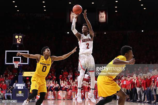 Kobi Simmons of the Arizona Wildcats attempts a shot over Tra Holder of the Arizona State Sun Devils during the first half of the college basketball...