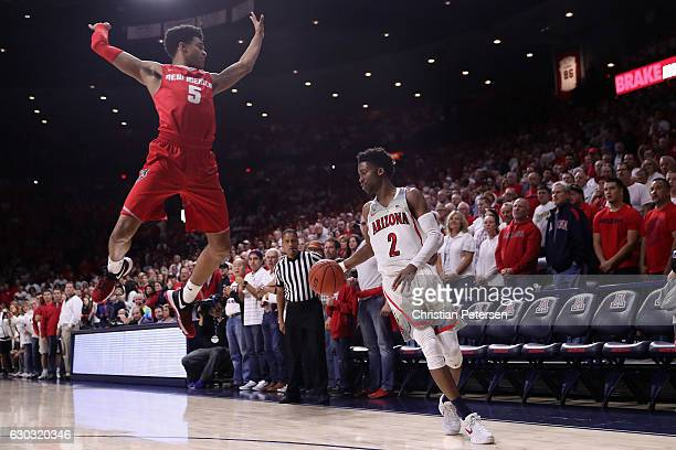 Kobi Simmons of the Arizona Wildcats handles the ball as Jalen Harris of the New Mexico Lobos leaps in during the first half of the college...