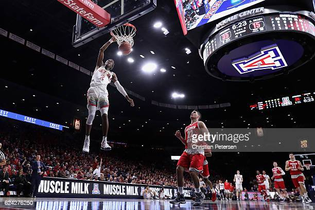 Kobi Simmons of the Arizona Wildcats slam dunks the ball ahead of Sean Hoehn of the Sacred Heart Pioneers during the first half of the college...